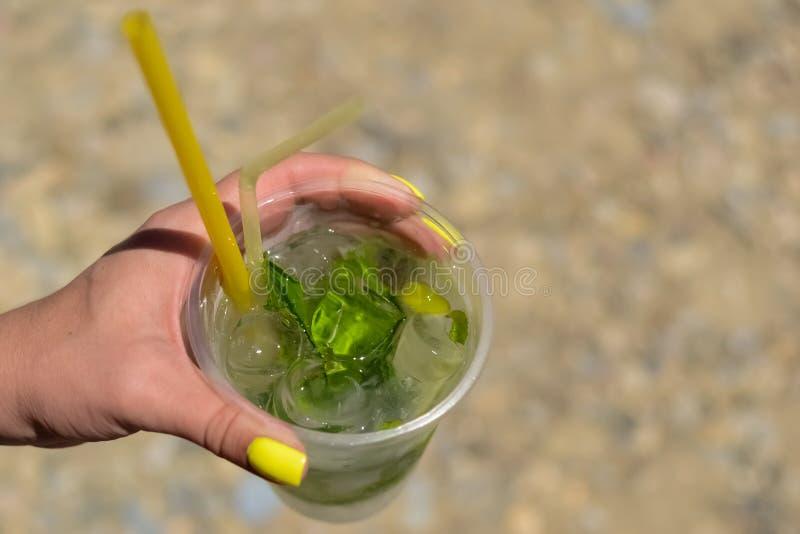 La première main du ` s tient un verre transparent de glace avec le citron et la menthe Mojito photos stock