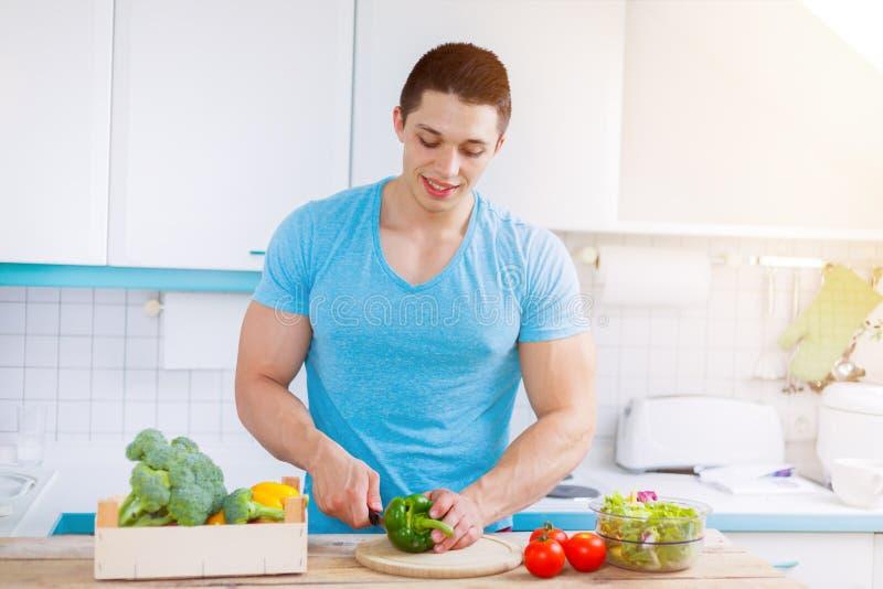 La preparación de la comida cortó al hombre joven de las verduras que la cocina sana de la comida come imagen de archivo