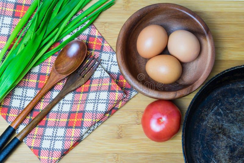 La preparación de los ingredientes para cocinar el pollo eggs en una cacerola vieja imagen de archivo libre de regalías
