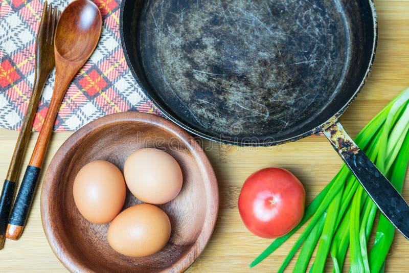 La preparación de los ingredientes para cocinar el pollo eggs en una cacerola vieja foto de archivo libre de regalías