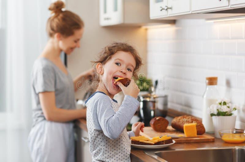 La preparación de la madre del desayuno de la familia y la hija del niño cocinan foto de archivo