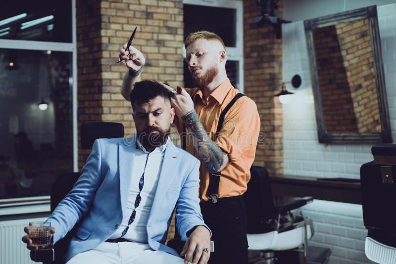 La preparazione dei capelli è appena per precipitarsi la screpolatura Cliente alla moda barbuto del negozio di barbiere Negozio d fotografia stock libera da diritti