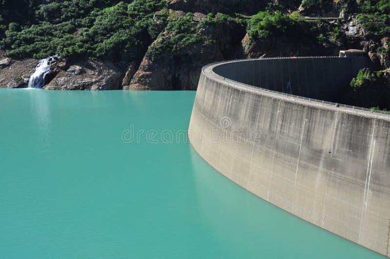 La presa concreta artificial, lago verde de la montaña riega foto de archivo