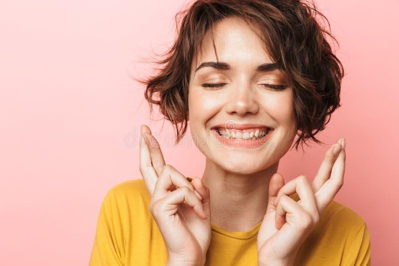 La presentación hermosa emocionada de la mujer aislada sobre fondo rosado de la pared para hacer los fingeres esperanzados del ge fotografía de archivo