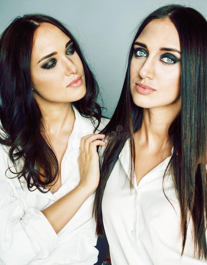 La presentaci?n de la muchacha de dos gemelos de las hermanas, haciendo el selfie de la foto, visti? la camisa blanca, amigos div imagenes de archivo