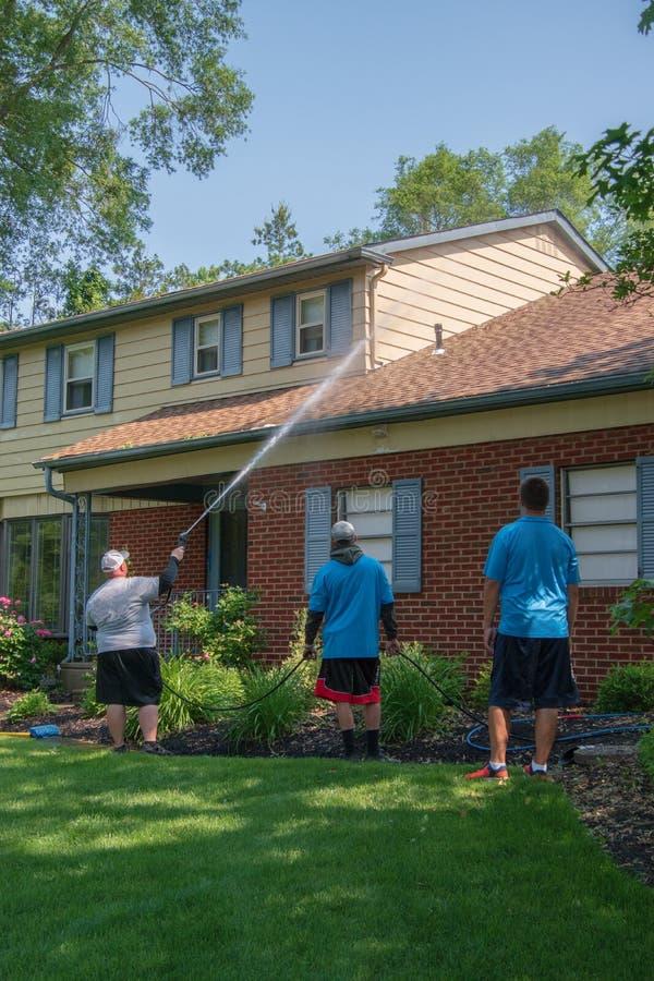 La pression d'homme lave la voie de garage sur sa maison avec sa observation de deux fils adolescents L'homme pulvérise l'eau sur photos stock
