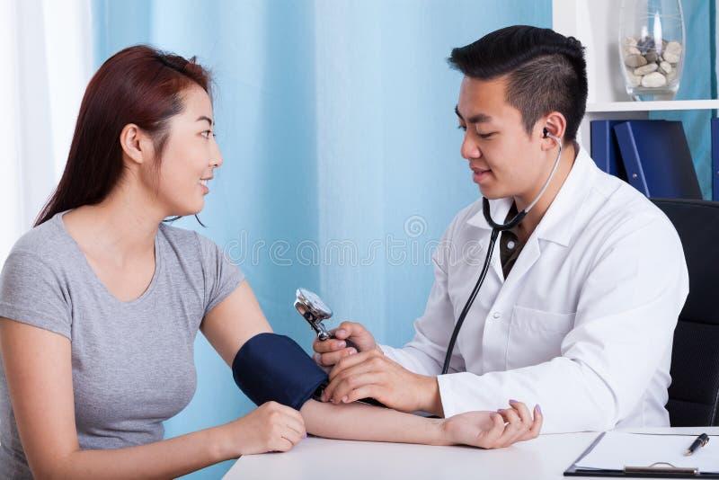 La pressione del paziente di misurazione di medico asiatico fotografia stock libera da diritti