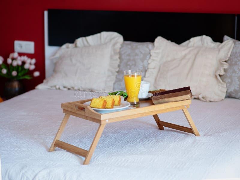 La prima colazione è servito a letto su un vassoio di legno con tè, succo, biscotti Il servizio di camera di albergo, si rilassa  immagini stock