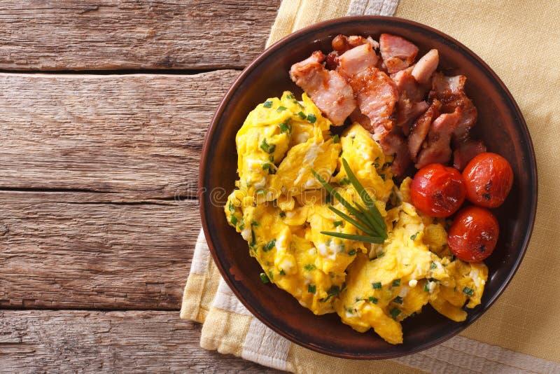 La prima colazione è uova rimescolate con la erba cipollina, primo piano fritto del bacon Uff fotografie stock libere da diritti