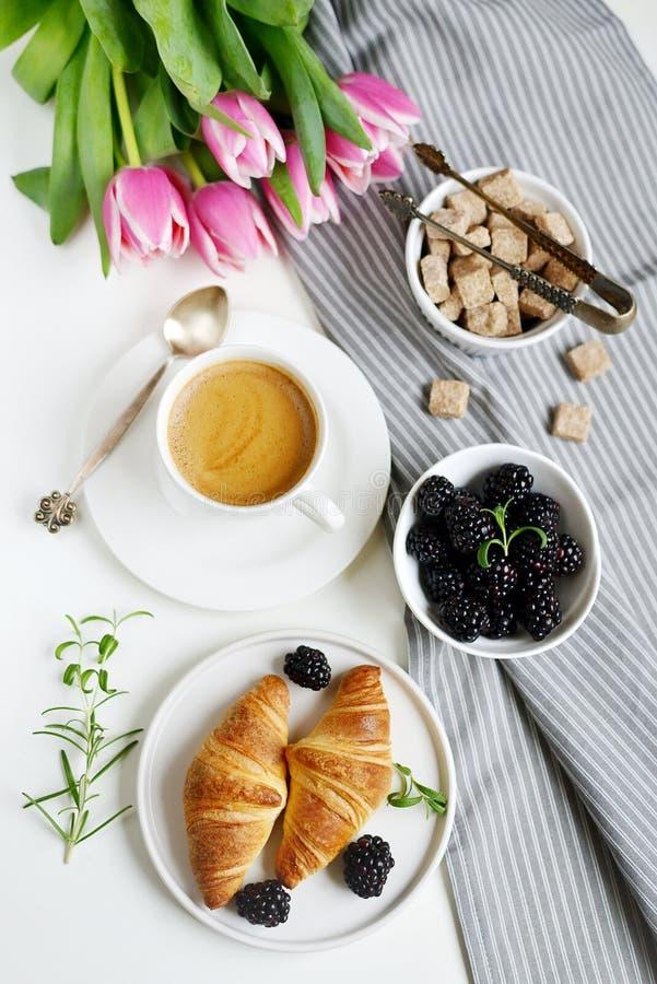La prima colazione di mattina con la tazza di caffè, i croissant, le bacche fresche ed il rosa fiorisce i tulipani fotografie stock libere da diritti