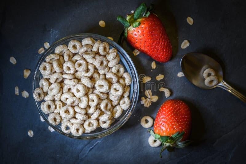La prima colazione ha composto di cereale asciutto con le fragole rosse fotografia stock libera da diritti