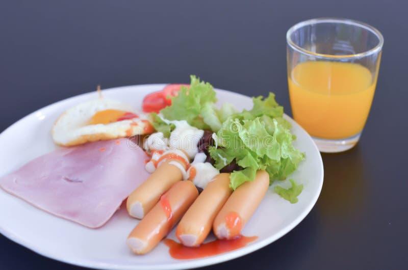 La prima colazione ha messo in piatto con succo d'arancia sulla tavola grigia fotografia stock