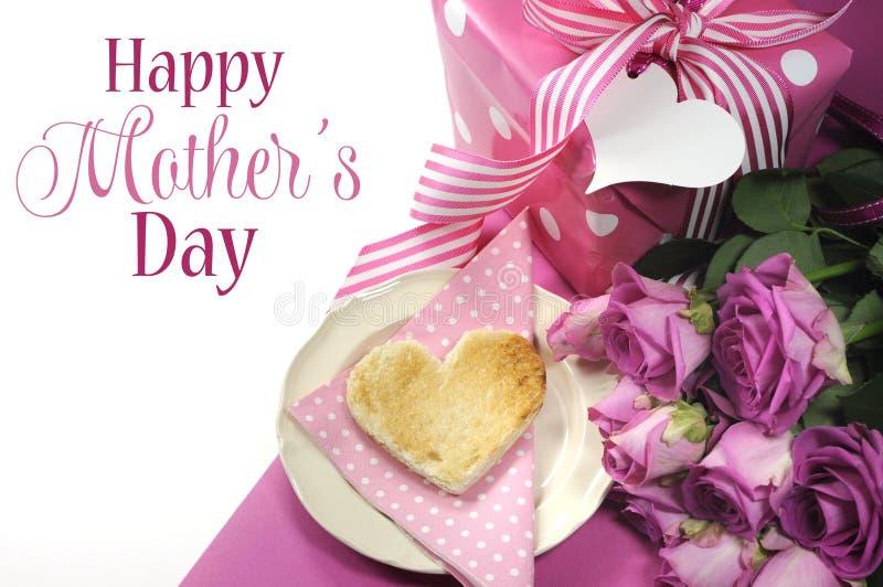 La prima colazione rosa di tema con cuore ha modellato il pane tostato, le rose ed il regalo del pois con buona Festa della Mamma fotografia stock