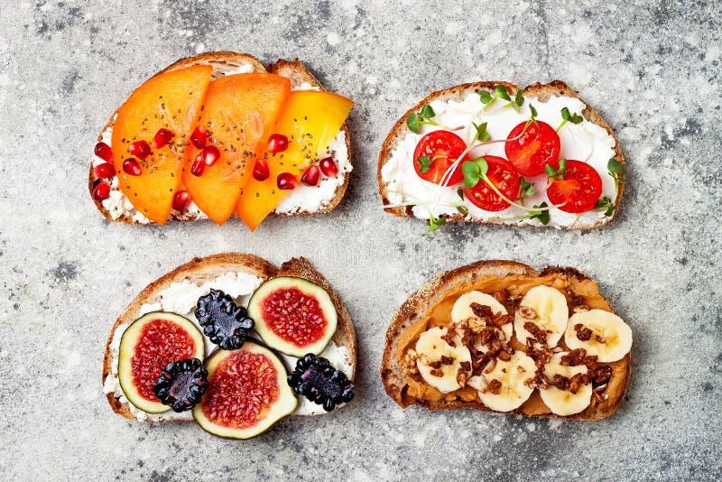 La prima colazione sana tosta con burro di arachidi, la banana, il granola del cioccolato, l'avocado, il cachi, i semi di chia, f immagini stock libere da diritti