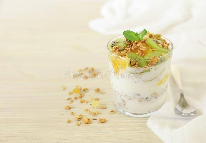 La prima colazione saporita e sana o fa un spuntino un vetro di yogurt, granola ed il kiwi, l'arancia, le fette della banana, il  fotografie stock libere da diritti