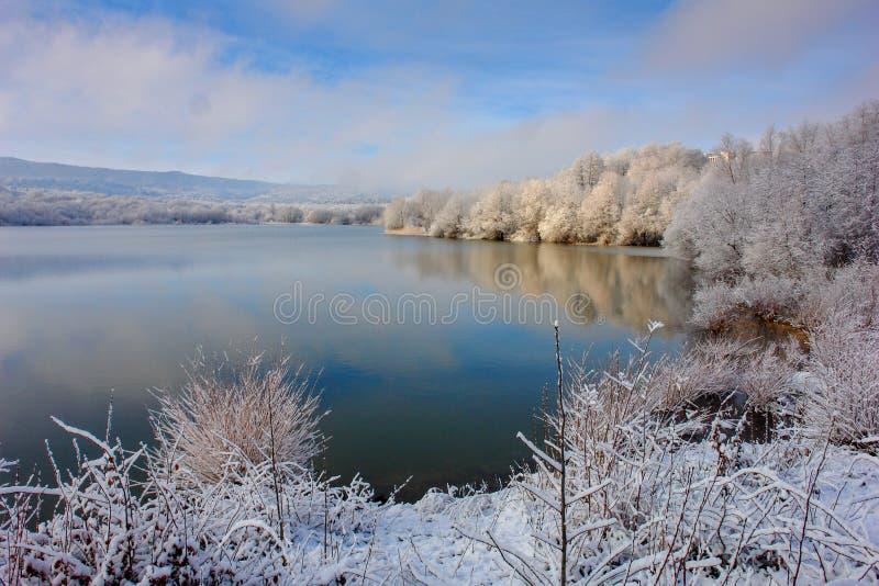 La prima neve su un lago della montagna immagine stock