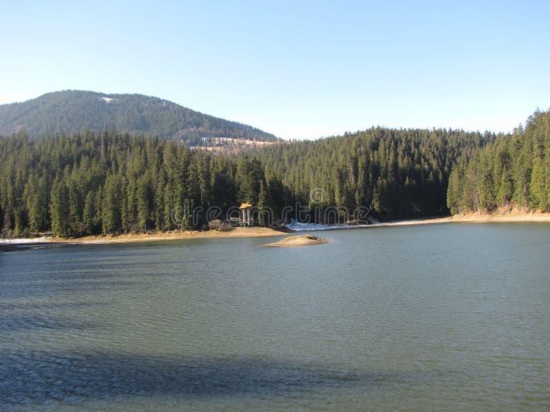 La prima neve vicino ad un lago della montagna fotografie stock libere da diritti