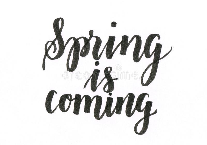 La primavera está viniendo - mano que pone letras a la inscripción en negro ilustración del vector