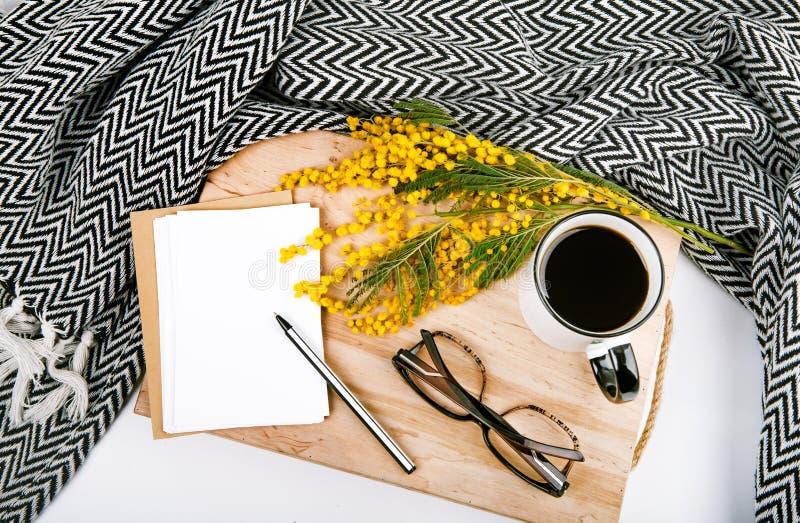 La primavera fijó con el vidrio amarillo de la pluma del café de la taza de la tela escocesa de la mimosa de las flores imagen de archivo