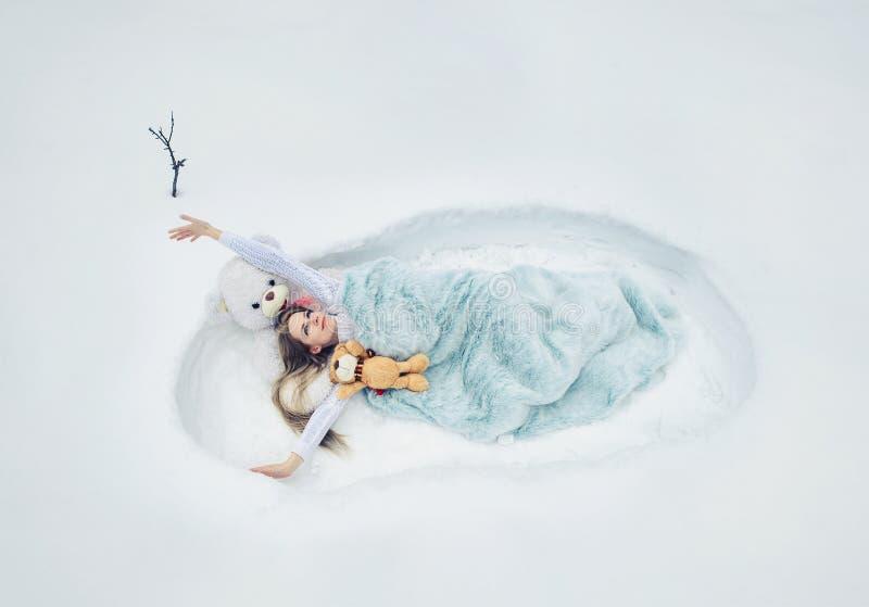 La primavera ha despertado, la mujer pone en un nevado con una manta, un sueño mullido y acogedor suave, ropas de cama foto de archivo libre de regalías