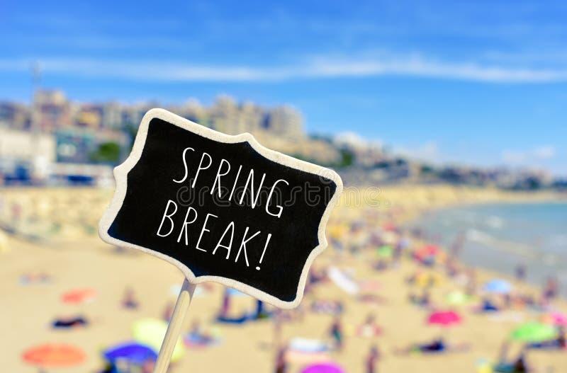 La primavera irrompe un'insegna nera sulla spiaggia immagine stock libera da diritti