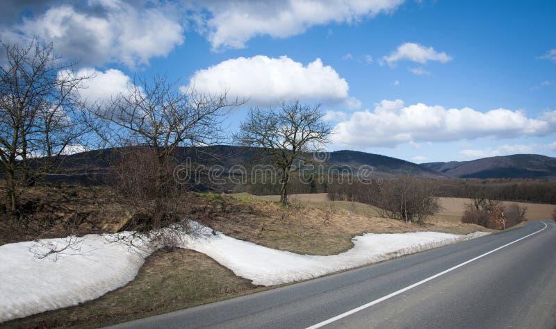 La primavera temprana es los remanente de la nieve en la cuesta del camino en las montañas fotos de archivo libres de regalías
