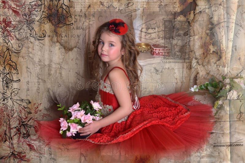 La princesa de la niña en un vestido rojo y un sombrero se sienta en el sofá w foto de archivo