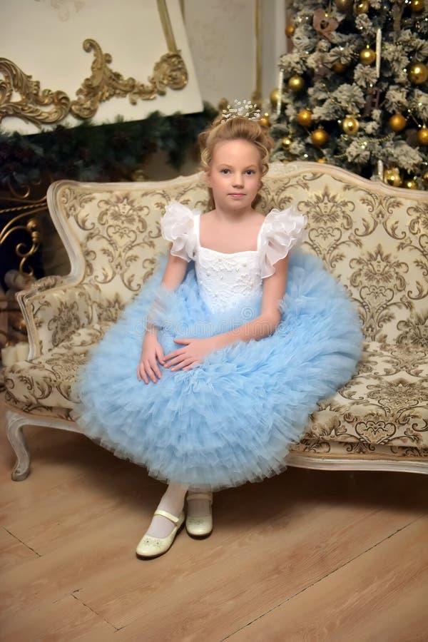 La princesa en blanco con el vestido elegante azul se sienta en una butaca imagen de archivo
