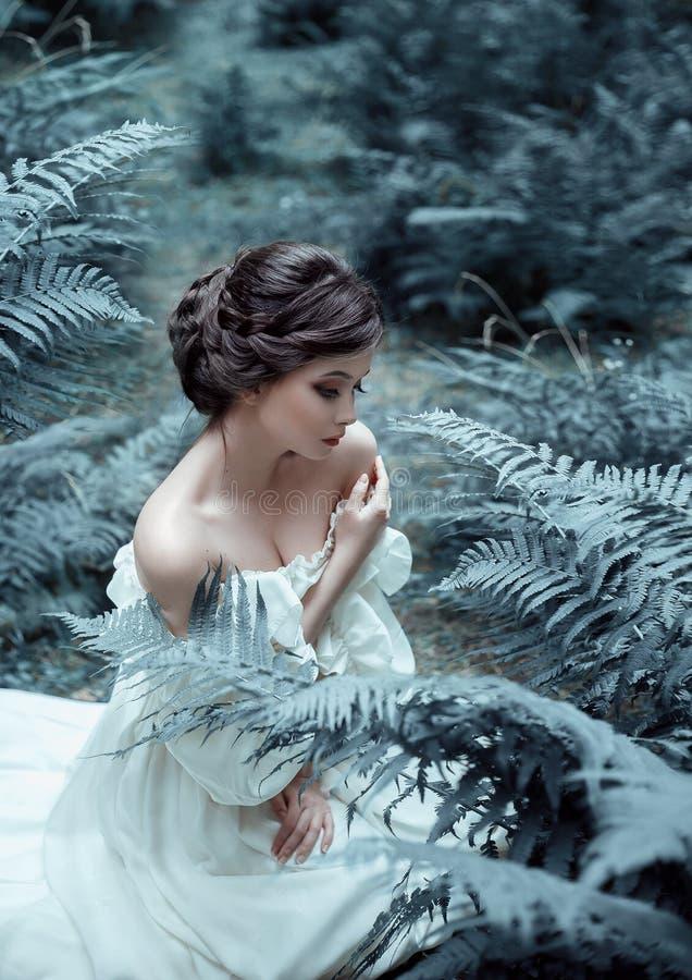La princesa se sienta en la tierra en el bosque, entre el helecho y el musgo Una cara inusual En la señora es un vintage blanco imagen de archivo