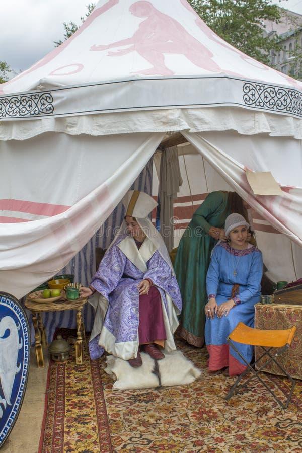 La princesse et la domestique dans des robes historiques antiques s'asseyent sur le tapis turc lumineux dans une tente blanche fe images libres de droits