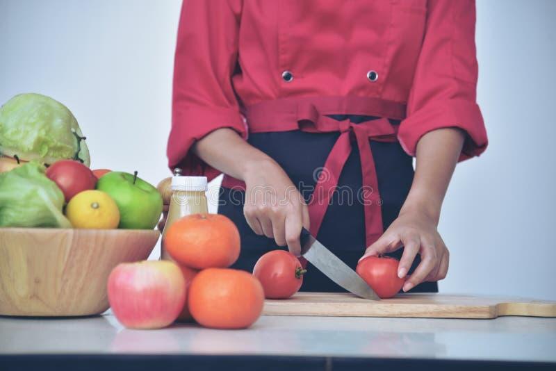 La principal hembra asiática encantadora bonita prepara la cocina sana del estilista de la comida cocina uniforme del cocinero imagenes de archivo