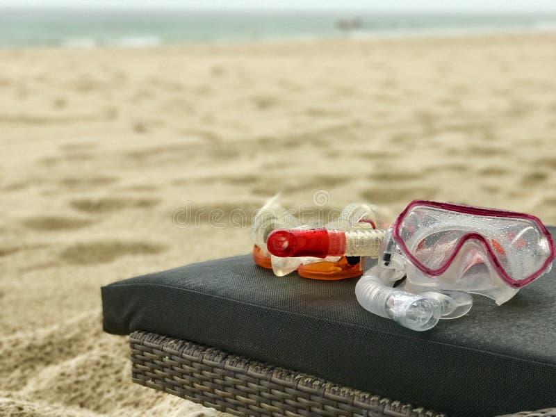 La prise d'air et le masque de plongée sur une chaise longue sur un sable blanc échouent photographie stock