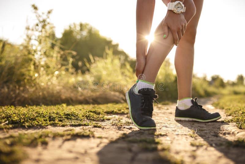 La prise de coureur de femme ses sports a blessé la jambe photo stock