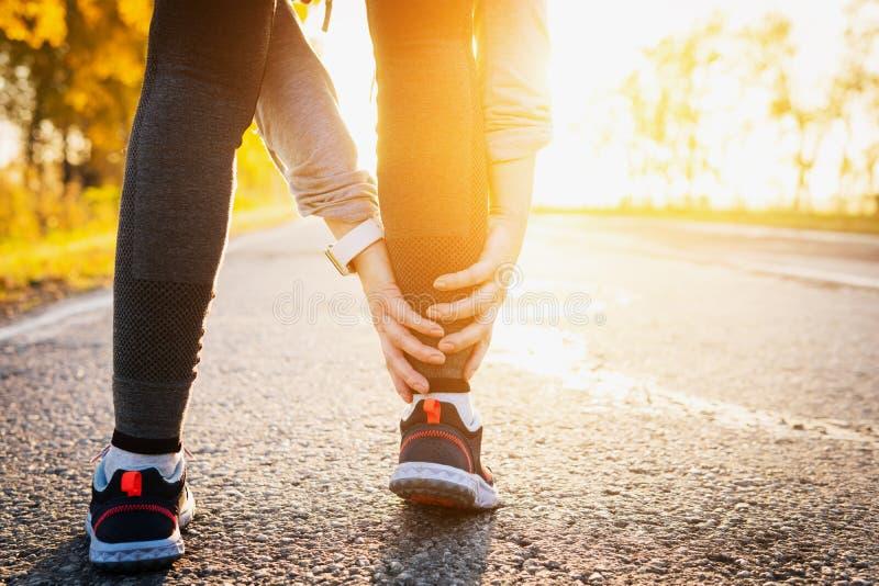 La prise de coureur de femme ses sports a blessé la jambe Plan rapproché de jambe extérieur photographie stock libre de droits