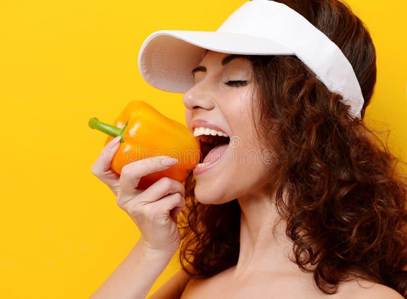 La prise de femme et mangent du paprika orange de poivre dans le chapeau blanc photo stock