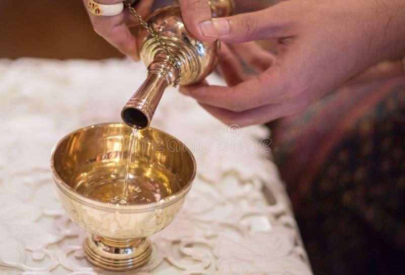 La prise de jeunes mariés le Graal et versement de l'eau de versement dans le bouddhisme traditionnel thaïlandais de cérémonie de photo stock