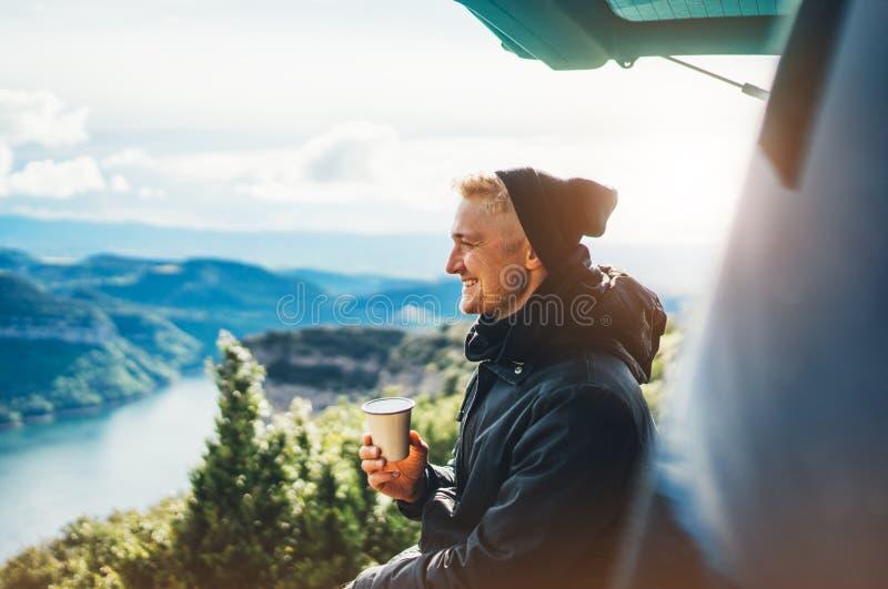 La prise de touristes de hippie dans la tasse de mains de la boisson chaude, sourire isolé de type apprécient la montagne de fusé photo stock