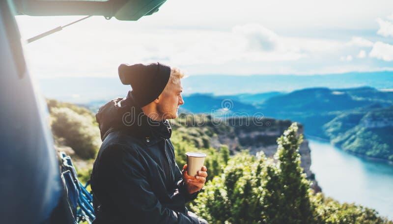 La prise de touristes de hippie dans la tasse de mains de la boisson chaude, type seul apprécient la montagne de fusée du soleil  image stock