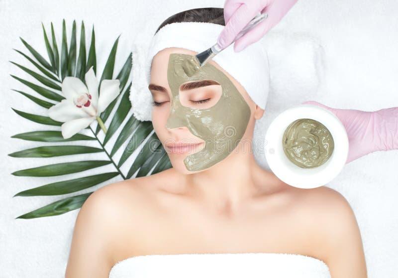 La procedura per l'applicazione della maschera dall'argilla al fronte di bella donna immagine stock