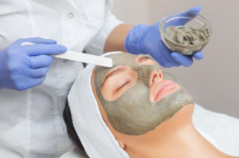 La procedura per l'applicazione della maschera dall'argilla al fronte di bella donna immagine stock libera da diritti
