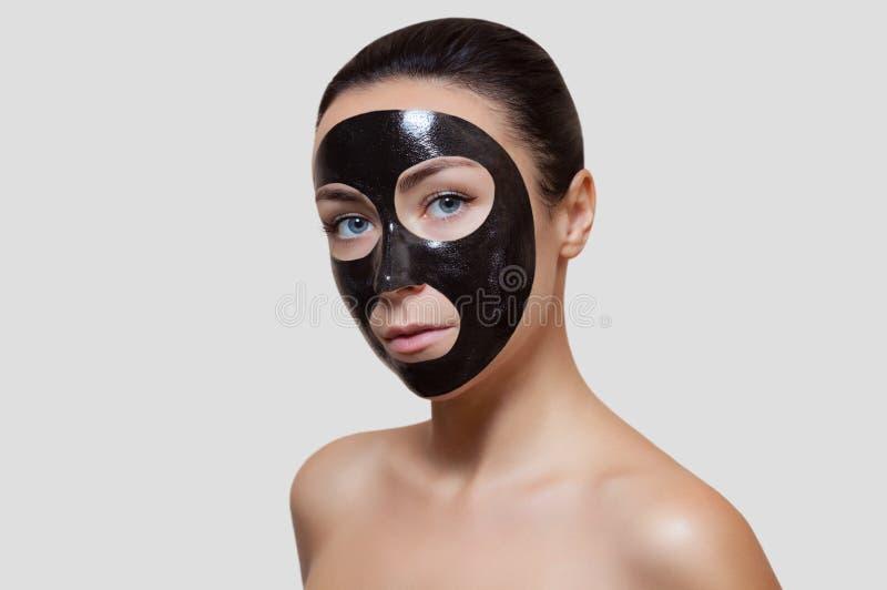 La procedura per l'applicazione della maschera nera al fronte di bella donna immagine stock