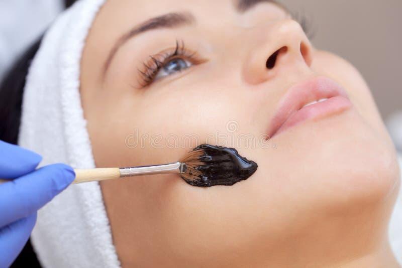 La procedura per l'applicazione della maschera nera al fronte di bella donna immagine stock libera da diritti