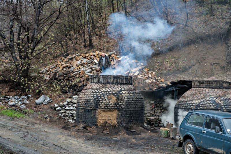 La producción de carbón de leña de una manera tradicional en el bosque fotos de archivo