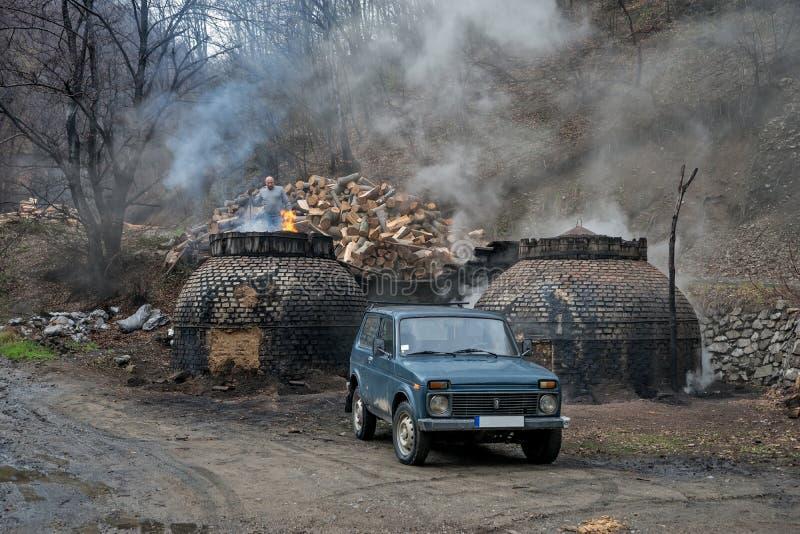 La producción de carbón de leña de una manera tradicional en el bosque imagen de archivo