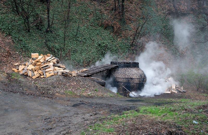 La producción de carbón de leña de una manera tradicional en el bosque foto de archivo