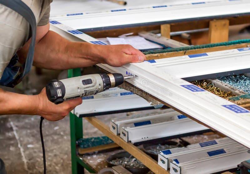 La producción de ventanas del pvc, un hombre atornilla un destornillador en una ventana del pvc, primer, pvc de las ventanas fotografía de archivo