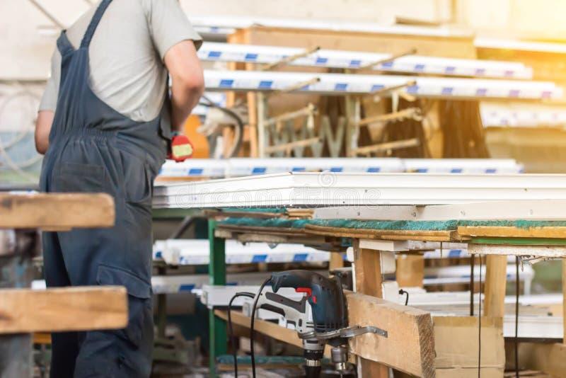La producción de ventanas del pvc, un hombre recoge una ventana del pvc, un destornillador, trabajador imagenes de archivo
