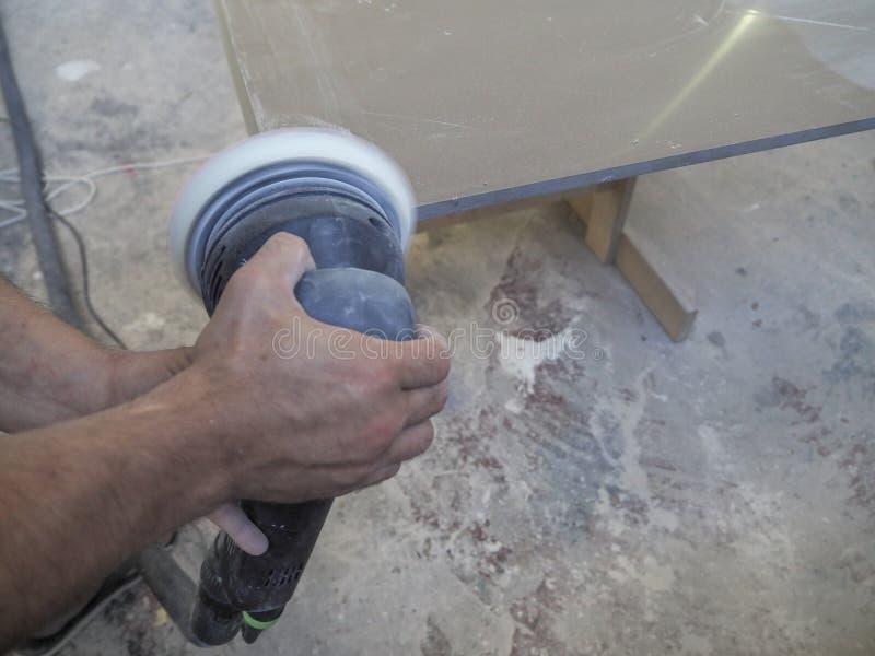 La producción de worktops de acrílico en una fábrica de los muebles Un trabajador produce encimeras de acrílico en la fábrica Pul foto de archivo