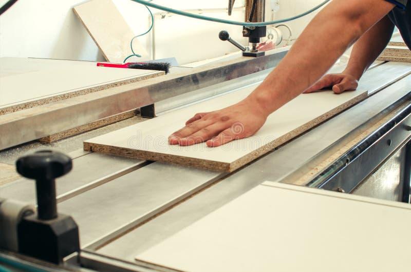 La production des meubles de coffret, coupant partie sur une machine de format photos stock