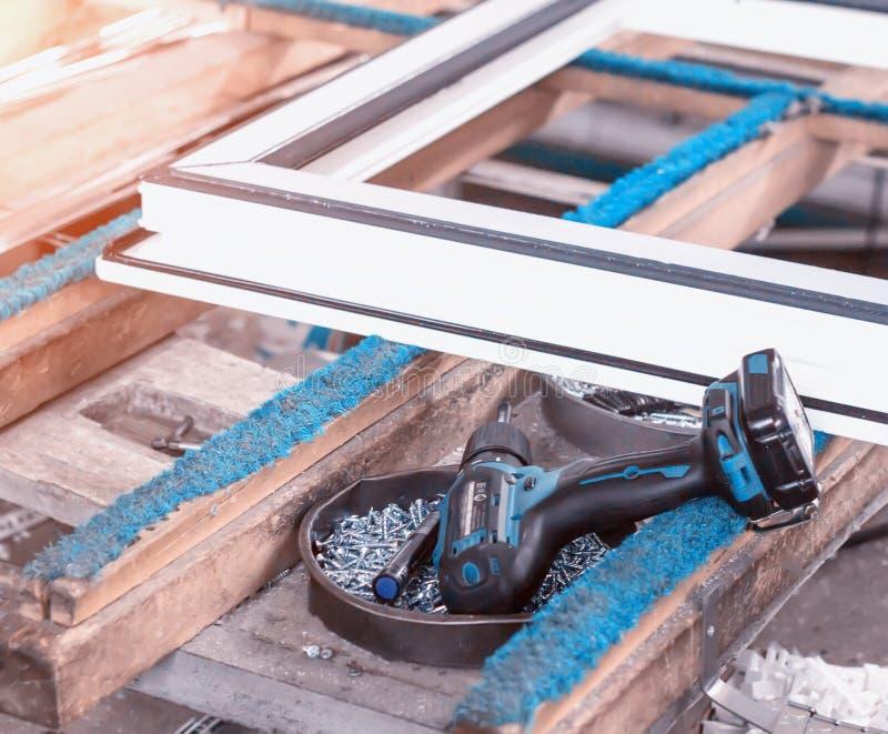 La produzione delle finestre del PVC, cacciavite si trova vicino alla struttura del PVC, fabbricazione delle finestre di plastica fotografie stock